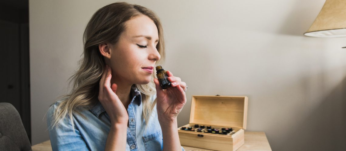 Young,Woman,Applying,Essential,Oils,To,Her,Neck,And,Smelling